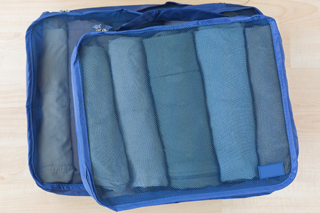 Photo pour Cube meshed bags with rolled clothes, t-shirt, pants. Set of travel organizer to help packing luggage easy, well organized - image libre de droit