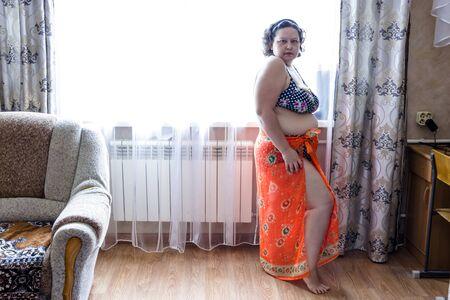 Foto de pictured in the photo plump woman in a purple swimwear and orange pareo - Imagen libre de derechos