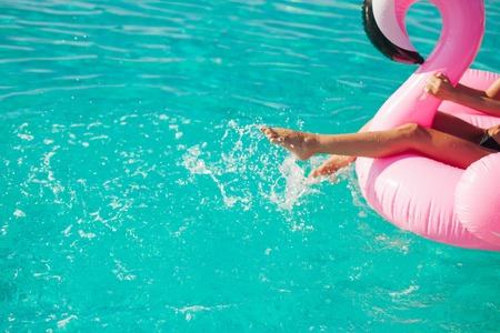 Photo pour Tan girl sits on inflatable mattress flamingos in the pool - image libre de droit