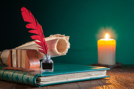 Photo pour Quill pen, inkwell and a rolled papyrus sheet on an old book by candle light - image libre de droit