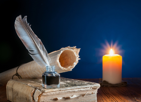 Photo for Quill pen, inkwell and a rolled papyrus sheet on an old book by candle light - Royalty Free Image