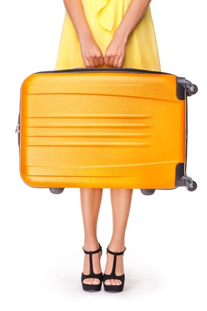 Foto de Girl stands with orange suitcase and ready to travel - Imagen libre de derechos