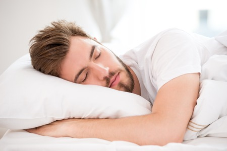 Photo pour Handsome young man with a beard sleeping in white bed - image libre de droit
