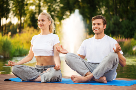 Young happy couple practising yoga and sitting in lotus pose with a beautiful green scenery of park on background