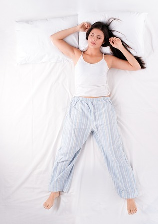 Photo for Beautiful young woman sleeping in free fall position on white bed - Royalty Free Image