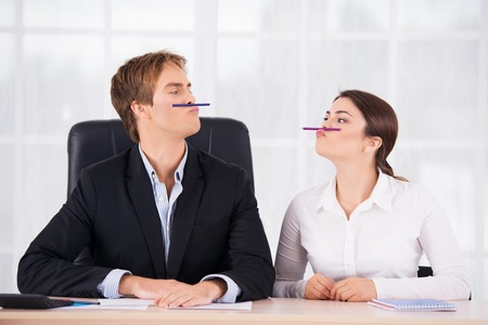 Foto de Young business woman and man having fun on working place with pen upper lips - Imagen libre de derechos