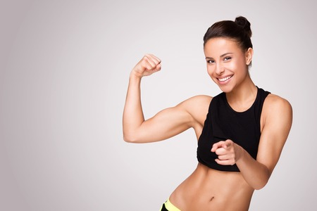 Foto per Cheerfully smiling mixed race sporty woman demonstrating biceps, isolated on white background - Immagine Royalty Free
