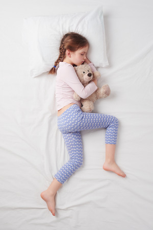 Photo for Top view photo of little cute girl sleeping on white bed and hugging teddy bear. - Royalty Free Image