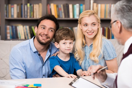 Foto de Young family of three talking with psychologist. Psychologist taking notes. There are many books in psychologist office - Imagen libre de derechos