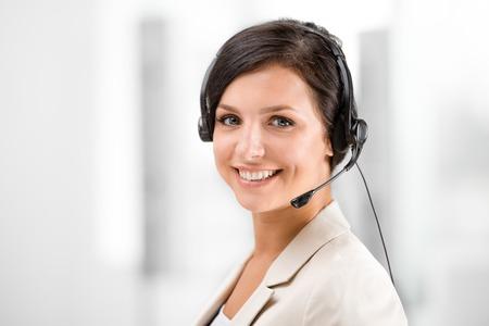 Foto de Beautiful smiling woman with headphones looking at camera at office - Imagen libre de derechos