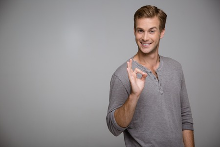 Photo for Portrait of handsome stylish young man on grey background. Man looking at camera, cheerfully smiling and showing ok sign. Horizontal photo - Royalty Free Image