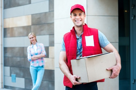 Foto de Colorful picture of courier delivers package for woman. Courier holding the box. Woman stands behind the courier. They are looking at camera and smiling. - Imagen libre de derechos
