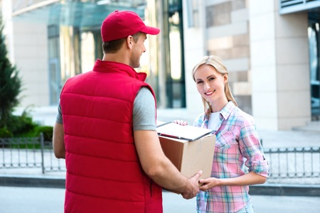 Photo pour Colorful picture of courier delivers package for woman. Woman accepts the parcel and smiling. - image libre de droit