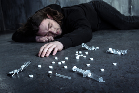 Foto de Photo of desperate young drug addict lying alone in dark after taking heroin and pills - Imagen libre de derechos