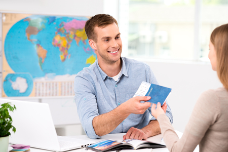 Photo pour Photo of male travel agent and young woman. Young man smiling and giving tickets, passport with visa to female tourist. Travel agency office interior with big world map - image libre de droit