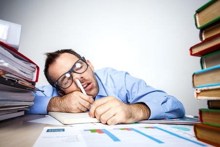 Photo pour Funny photo of businessman with beard wearing shirt and glasses. Overworked businessman sleeping at table full of documents with pen in his nose. Isolated on white background - image libre de droit