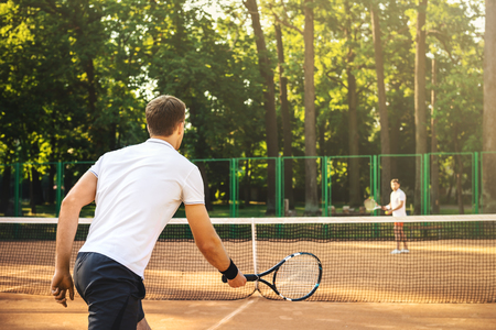 Photo pour Picture of handsome young men on tennis court. Men playing tennis. Man is ready to hit tennis ball. Beautiful forest area as background - image libre de droit