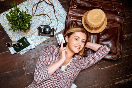 Foto de Top view photo of beautiful blonde girl lying on wooden floor. Young woman smiling, holding credit card and looking at camera. Passport, tickets, vintage camera, hat and map are on floor - Imagen libre de derechos