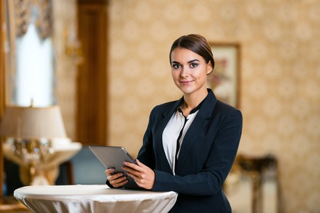 Photo for Young business woman wearing suit, standing in nice hotel room, using tablet computer and looking at camera - Royalty Free Image