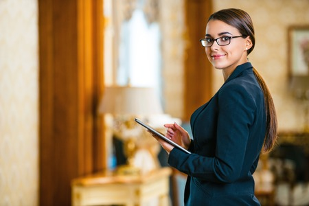 Photo for Young business woman wearing suit and glasses, standing in nice hotel room, using tablet computer and looking at camera - Royalty Free Image