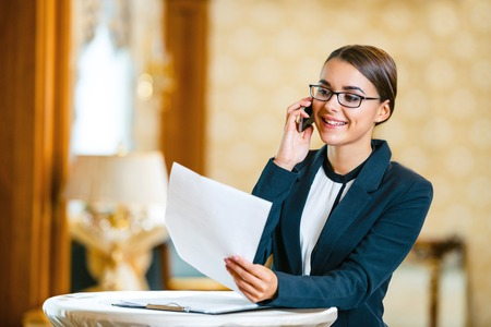 Photo pour Young business woman wearing suit and glasses, standing in nice hotel room, talking by phone and looking at documents - image libre de droit