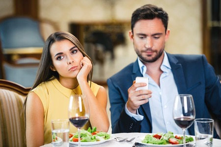 Photo for Young woman is bored and lonely while her boyfriend using mobile phone - Royalty Free Image