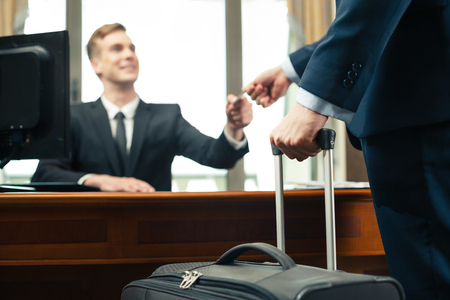 Photo for Customer with suitcase giving his credit card to receptionist - Royalty Free Image