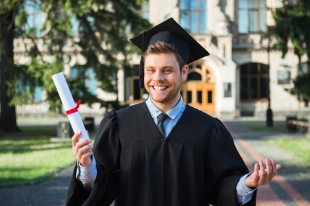 Photo pour Young male student dressed in black graduation gown. Campus as a background. Boy cheerfully smiling, holding diploma and looking at camera - image libre de droit