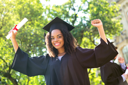 Foto de Young Afro American female student dressed in black graduation gown. Campus as a background. Girl cheerfully smiling with arms up, holding diploma and looking at camera - Imagen libre de derechos