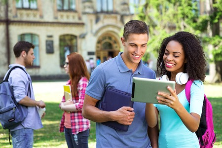 Foto de Photo of young group of students with backpacks and books. Campus as a background. Girl and boy using tablet computer. Students are on background - Imagen libre de derechos