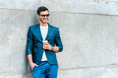 Photo for Portrait of stylish handsome young man with bristle standing outdoors. Man wearing jacket and shirt. Smiling man with sunglasses holding cup of coffee and leaning against wall - Royalty Free Image