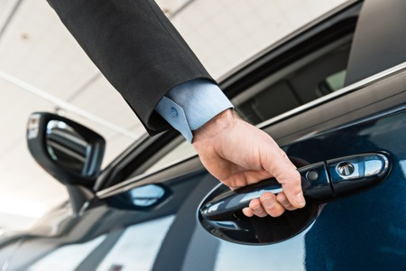 Photo pour Close up photo of young man hand touching and openning new car. Concept for car rental - image libre de droit