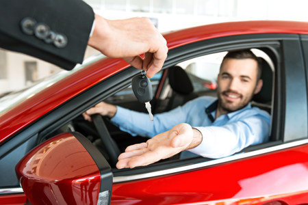 Photo pour Photo of young man sitting inside new car and getting keys to it. Concept for car rental - image libre de droit