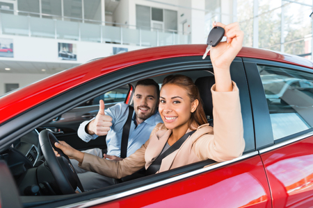 Photo pour Photo of young couple sitting inside new car. Woman holding keys to it. Man smiling and showing thumb up. Concept for car rental - image libre de droit