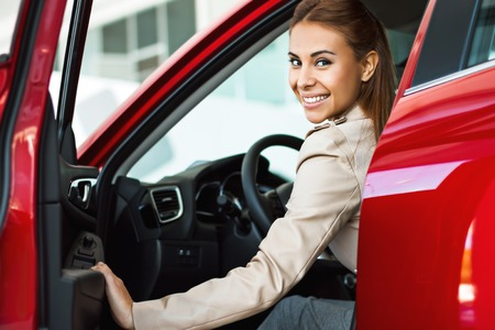 Photo pour Photo of happy young mixed race woman sitting inside her new car. Concept for car rental - image libre de droit