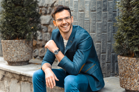 Foto de Portrait of stylish handsome young man with bristle standing outdoors. Man wearing jacket and watch. Man with glasses cheerfully smiling - Imagen libre de derechos