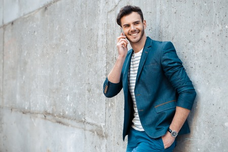 Foto de Portrait of stylish handsome young man with bristle standing outdoors and leaning on wall. Man wearing jacket and shirt. Smiling man using mobile phone - Imagen libre de derechos