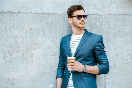 Photo pour Portrait of stylish handsome young man with bristle standing outdoors and leaning on wall. Man wearing jacket, sunglasses, shirt and holding cup of coffee - image libre de droit