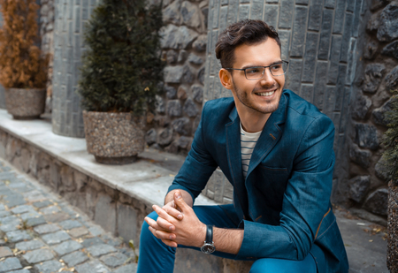 Foto de Portrait of stylish handsome young man with bristle sitting on parapet outdoors. Man wearing jacket and shirt - Imagen libre de derechos