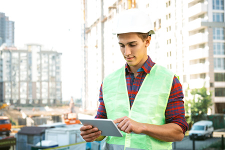Photo for Portrait of builder in uniform. Young man with helmet standing near new unfinished construction and using tablet computer - Royalty Free Image