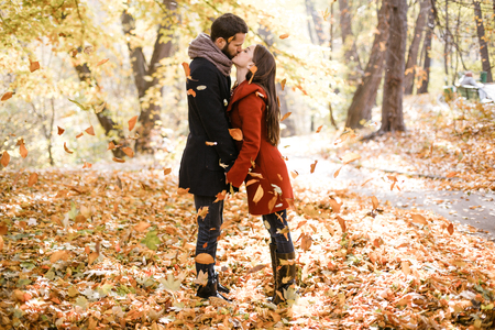 Foto per Romantic photo of cute couple outdoors in fall. Young man and woman kissing in falling leaves - Immagine Royalty Free