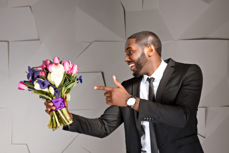 Photo for Portrait of handsome afro american man. Young stylish businessman smiling and pointing at nice bouquet of flowers. Man wearing suit and tie - Royalty Free Image