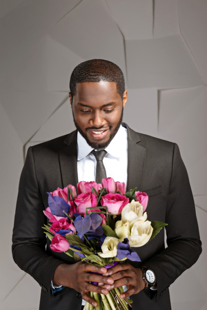 Photo for Portrait of handsome afro american man. Young stylish businessman smiling and looking at nice bouquet of flowers. Man wearing suit and tie - Royalty Free Image