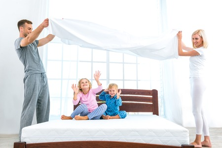 Photo pour Photo of loving family of four making bed. Young family demonstrating quality of mattress and holding blanket - image libre de droit