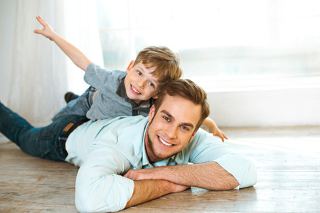 Foto de Nice family photo of little boy and his father. Boy and dad smiling and lying on wooden floor. Boy riding piggyback - Imagen libre de derechos
