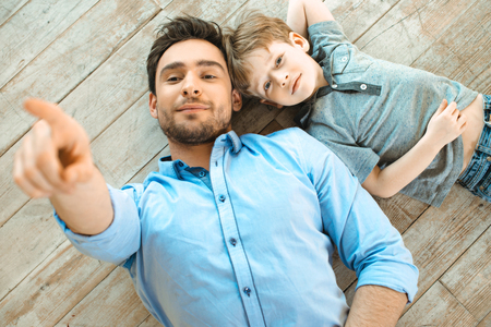 Photo pour Nice family photo of little boy and his father. Boy and dad smiling and lying on wooden floor. Father pointing at camera - image libre de droit