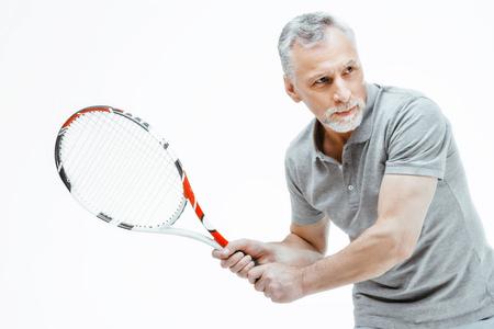 Photo pour Horizontal photo of silver haired senior sportsman isolated on white background. Man playing tennis - image libre de droit