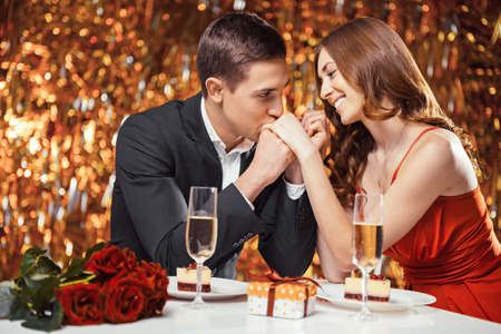 Foto de Romantic photo of beautiful couple on glitter gold background. Couple having date at Valentine's Day. Lovers having dinner. There are glasses with champagne, desserts, roses and gift on table - Imagen libre de derechos