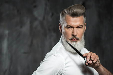 Photo pour Portrait of stylish professional hairdresser with beard. Man wearing shirt, looking aside and holding scissors near his beard - image libre de droit