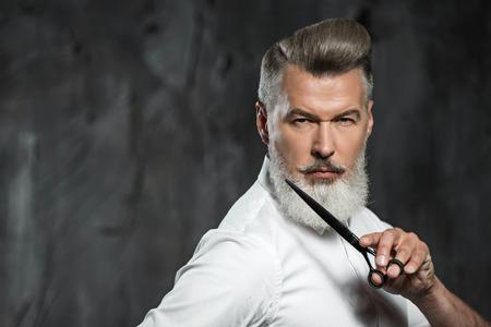 Foto de Portrait of stylish professional hairdresser with beard. Man wearing shirt, looking aside and holding scissors near his beard - Imagen libre de derechos